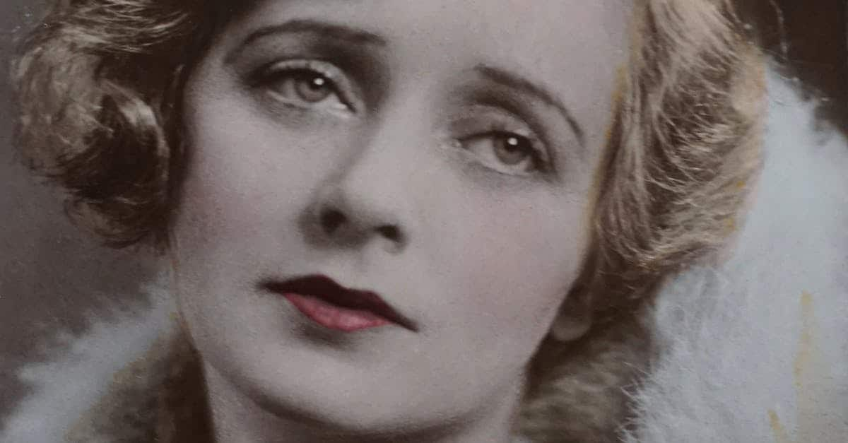 A close up of Evelyn Laye with pink hair looking at the camera